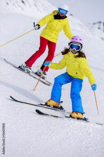 Skiing, skiers on ski run - child skiing downhill