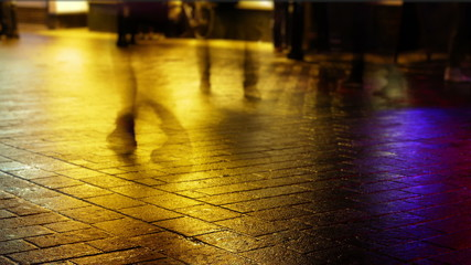 Time lapse of feet on a street backlit by colourful lights