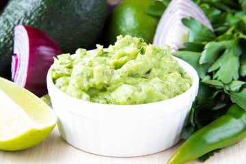 Green Mexican guacamole with avocado, lime, parsley and onion