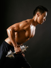 Asian man exercising with dumbbell