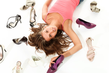 Girl between many shoes, portrait in studio