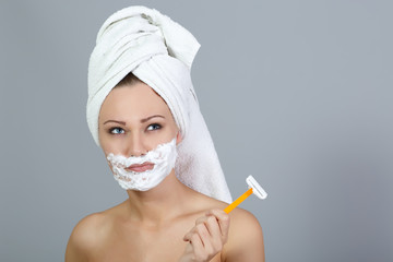 Thoughtful girl shaving face at gray background