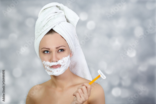 Thoughtful girl shaving face