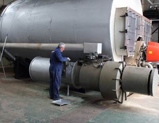 An engineer painting a large industrial steam boiler