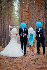 groom, bride and witnesses walking in autumn pine forest
