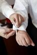 Trauzeuge hilft Bräutigam beim Anziehen
