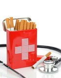Cigarettes in a red first aid tin with doctors stethoscope
