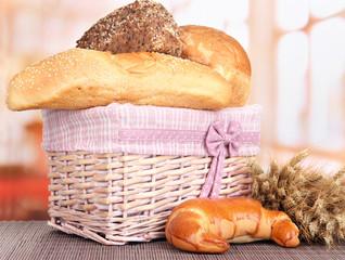 Baked bread in wicker basket on window background