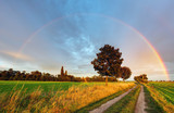 Fototapety Rainbow over field road