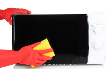 Hand with sponge cleaning  microwave oven, isolated on white