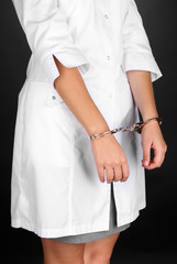Doctor in handcuffs on grey background