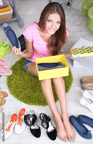 Beautiful girl chooses shoes in room