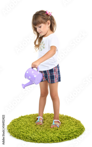Little girl watering green grass isolated on white
