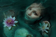 Beautiful woman in water with Lotus flowers