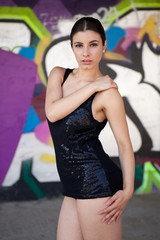 Beautiful girl with black top in front of graffiti wall