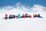Large group of kids laying in snow