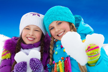 Two girls portrait holding snow hearts