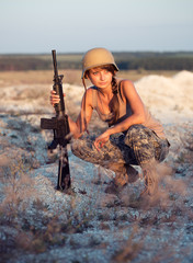 Female soldier dressed in a camouflage with a gun in the outdoor