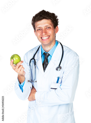 Portrait of a smiling male doctor holding green apple on white