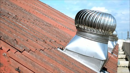 Row of spinning wind ventilators on old tiled roof [HD]