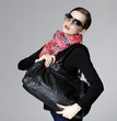 portrait of gorgeous young lady in sunglasses with bag