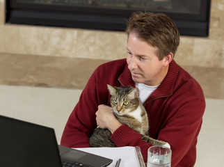 Mature man holding his family pet while working at home