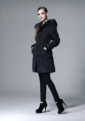 full length fashion model in black coat posing in studio