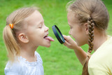 Fototapety Two little girls with magnifying glass outdoors in the day time