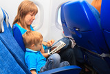 mother and son with touch pad in plane