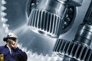 engineer examining large gears and cog machinery