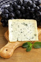 piece of blue cheese with grapes on a wooden board