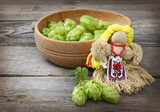 Doll motanka of thread and a bowl of freshly harvested hops on a