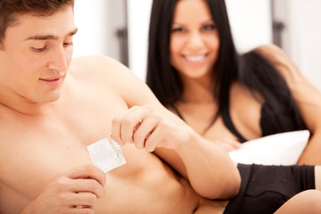 Young man opening condom with woman in bed