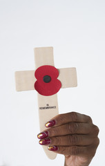 Woman's hand holding a cross and poppy