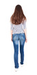 back view of walking  woman in jeans