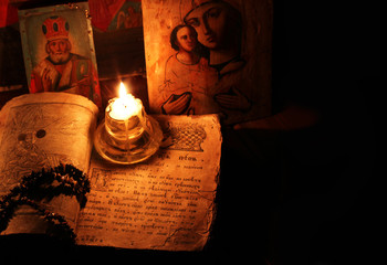 The religious book with icons and candles
