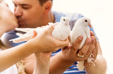 Kissing love couple with pare of white doves