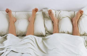 Pies sobre la cama.Pareja descansando en la cama.