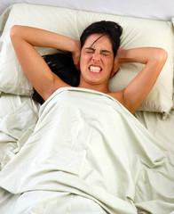 mujer en la cama molesta por ruido,dolor de cabeza