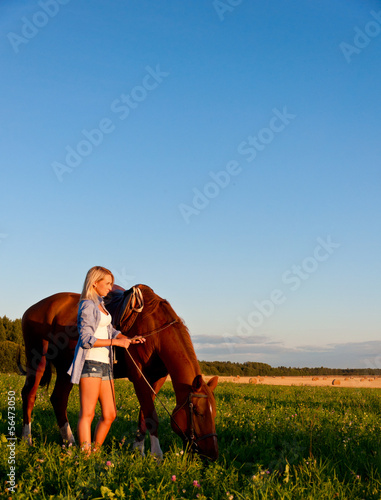 Young girl walking with a horse in the field