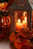 Lanterns with burning candles and pumpkins