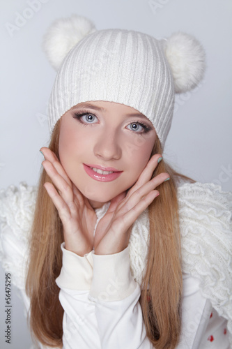 Beautiful teen girl wearing winter clothing and funny white hat.