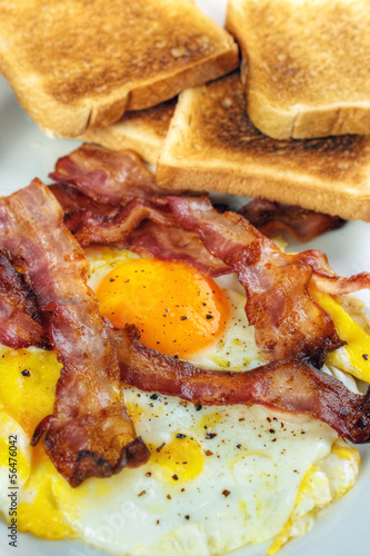 Fried egg and crispy bacon with toasts, vertical