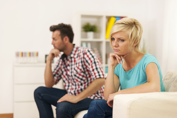 Unhappy young couple sitting in living room