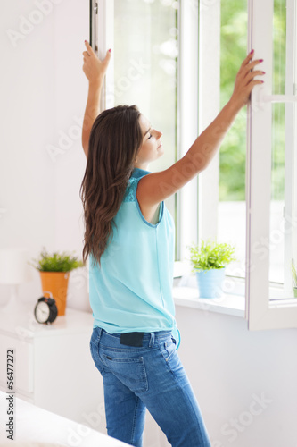 Young woman opening window in living room