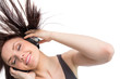 Smiling pretty brunette tossing her hair while listening to musi