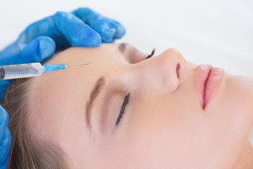 Surgeon making injection on womans forehead