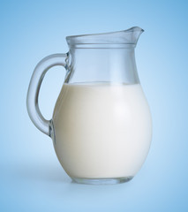 Milk glass jug on blue background