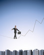 Businessman on a graph shaped tightrope
