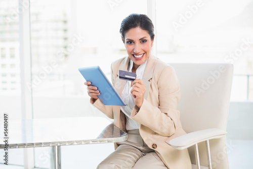 Excited businesswoman shopping online with tablet pc